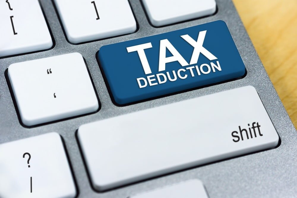 "Zoomed in view of a keyboard that shows a big blue key that reads ""TAX DEDUCTION"""