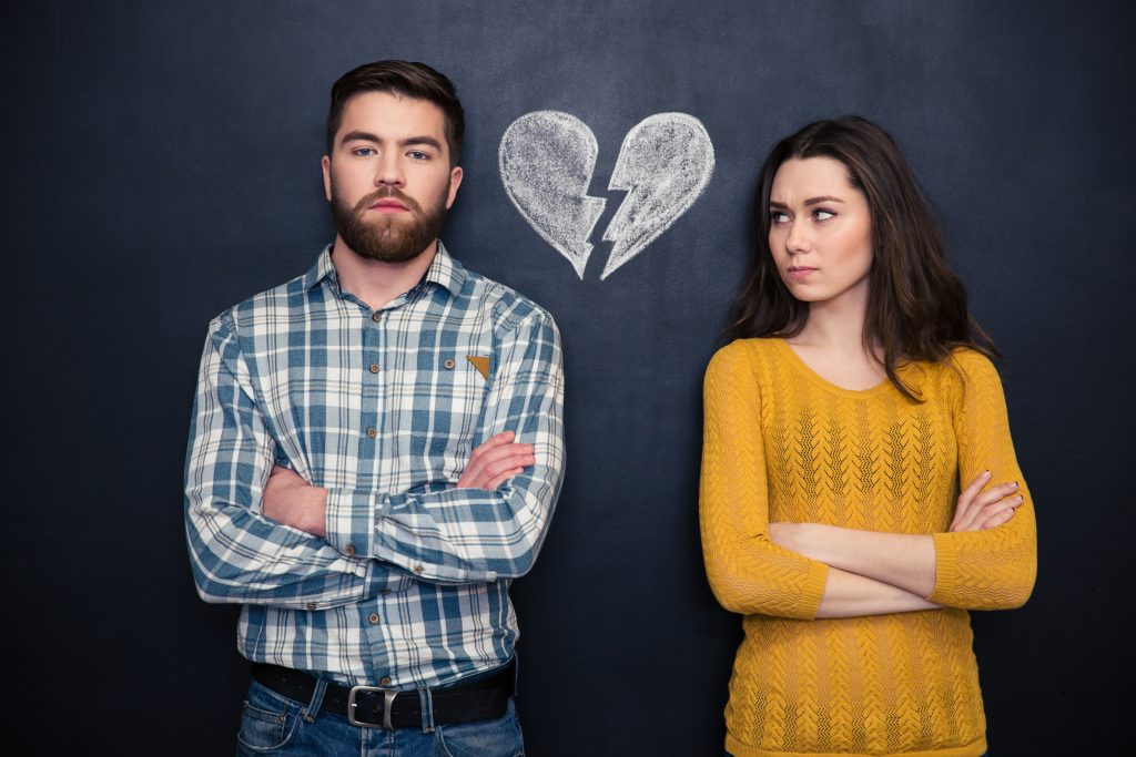 Portrait of young couple after argument standing separately with hands folded over blackboard background D