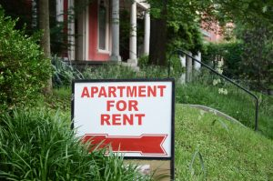 Apartment for rent sign displayed on residential street.