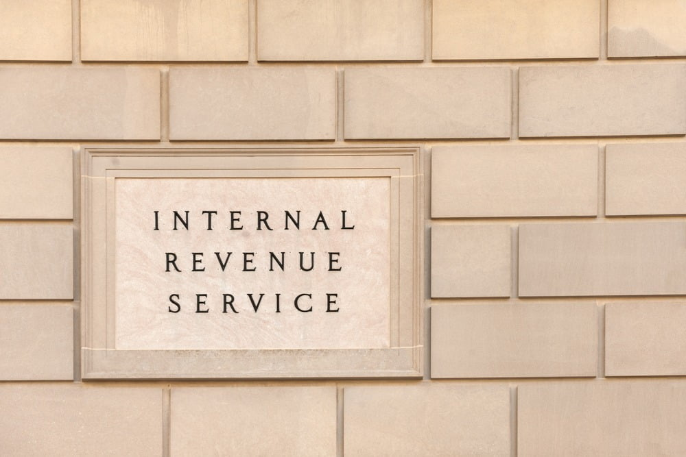 Close-up picture of the Internal Revenue Service sign on a tan brick wall.
