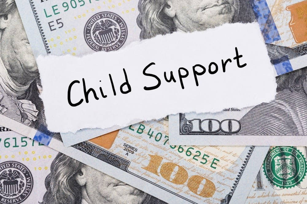 "The word ""Child Support"" on a piece of paper on top of a pile of money"