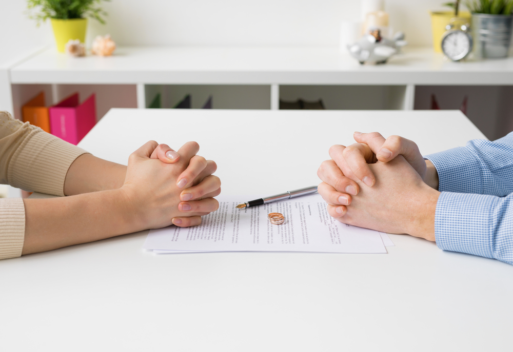 folded hands of a couple working on divorce papers