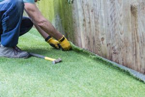 Artificial grass being installed. It has been cut to size and rolled out and laid and is being nailed down along a fence. The installer has a hammer and nails.