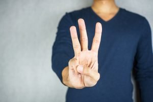 three finger salute hand gesture, on light grey background