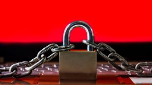Ransomware,Malware,Encrypt and Hacking Conceptual with Padlock.The Old padlock and Chains On Laptop with Red Screen.Ransomware stops and block access to a Computer and Data