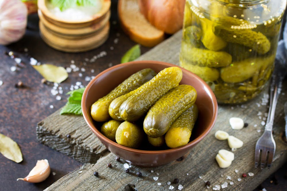 Green pickles in a tan bowl with ingredients in the background