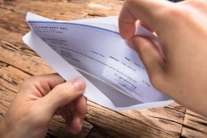 hands of businessman opening envelope with paycheck
