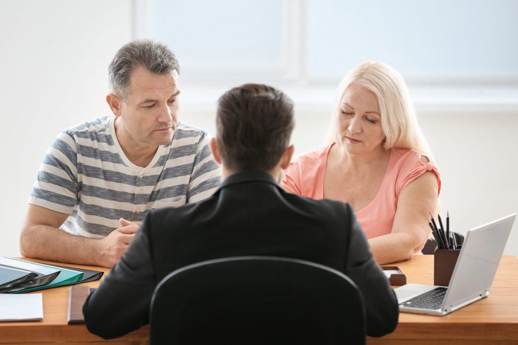 A middle aged Caucasian couple speaking with a businessman in his office.