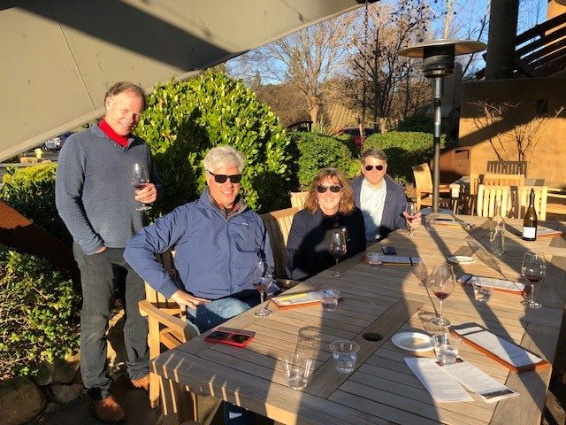 Pictured John Kirst John Duffy Mary Kay Redmond and Matthew D'Annunzio at Sixmilebridge Vineyards- All four people are sitting down at a table drinking red wine with bushes nd trees behind them- sun shining on them